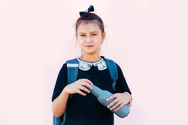 Nastoletnia dziewczyna trzyma butelkę wielokrotnego użytku na różowym tle.