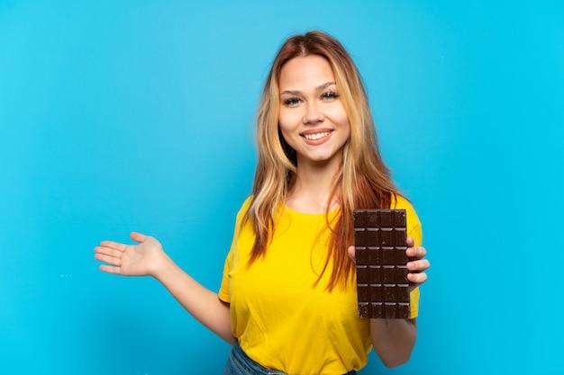 Nastoletnia dziewczyna trzyma czekoladę na białym tle niebieskiego, wyciągając ręce do boku, zapraszając do przyjścia