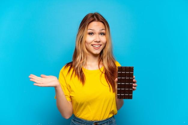 Nastoletnia dziewczyna trzyma czekoladę na białym tle z zszokowanym wyrazem twarzy