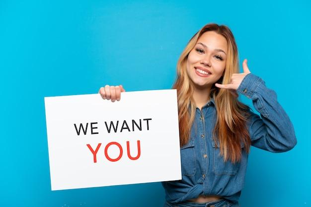 Nastoletnia dziewczyna trzyma deskę we want you i robi gest telefonem na odosobnionym niebieskim tle