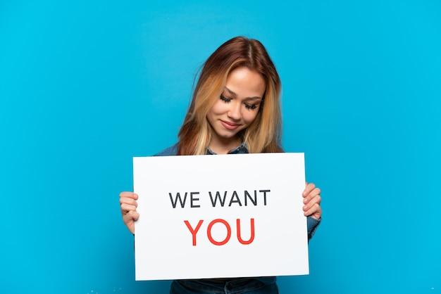 Nastoletnia dziewczyna trzyma deskę we want you na odosobnionym niebieskim tle