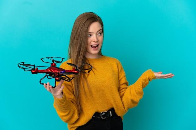 Nastoletnia dziewczyna trzyma drona na odosobnionym niebieskim tle z wyrazem zaskoczenia, patrząc z boku