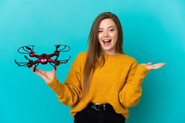 Nastoletnia dziewczyna trzyma drona na odosobnionym niebieskim tle ze zszokowanym wyrazem twarzy