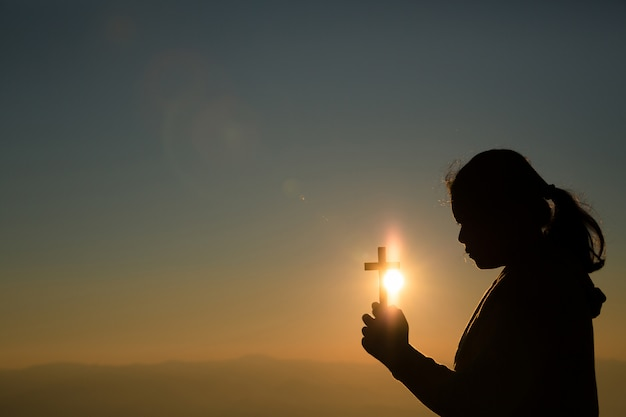 Nastoletnia dziewczyna trzyma krzyż z modleniem. pokój, nadzieja, koncepcja marzeń.