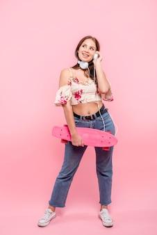 Nastoletnia dziewczyna trzyma longboard w ręce w hełmofonach