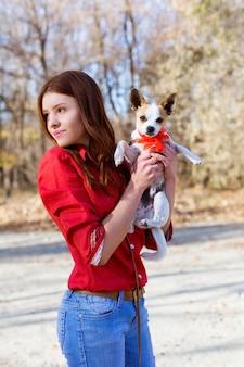 Nastoletnia dziewczyna trzyma małego psa-zabawkę teriera z czerwoną kokardą