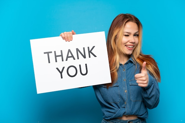 """Nastoletnia dziewczyna trzyma na białym tle niebieski napis z napisem """"dziękuję"""" i wskazuje do przodu"""