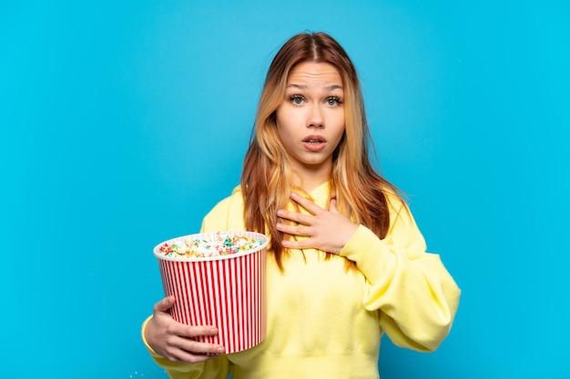 Nastoletnia dziewczyna trzyma popcorny na białym tle, zaskoczona i zszokowana, patrząc w prawo