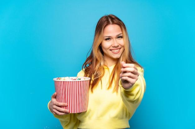 Nastoletnia dziewczyna trzyma popcorny na odosobnionym niebieskim tle robiąc gest pieniędzy