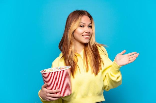 Nastoletnia dziewczyna trzyma popcorny na odosobnionym niebieskim tle, wyciągając ręce do boku, zapraszając do przyjścia