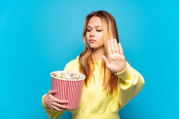 Nastoletnia dziewczyna trzyma popcorny na odosobnionym niebieskim tle, wykonując gest zatrzymania i rozczarowana