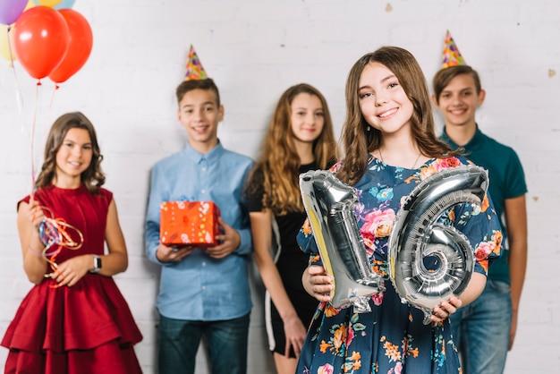 Nastoletnia dziewczyna trzyma popielatą liczbę 16 foliowego balonu liczby pozycję przed przyjaciółmi