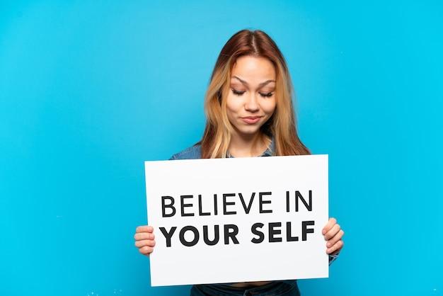 """Nastoletnia dziewczyna trzyma tabliczkę z tekstem """"uwierz w siebie"""" na białym tle niebieski"""
