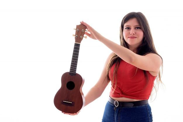Nastoletnia dziewczyna trzyma ukelele z jej ręką