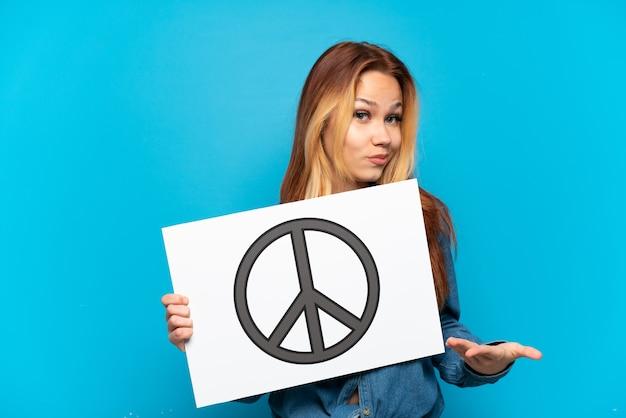 Nastoletnia dziewczyna trzymająca afisz z symbolem pokoju i wskazująca go na odosobnionym niebieskim tle