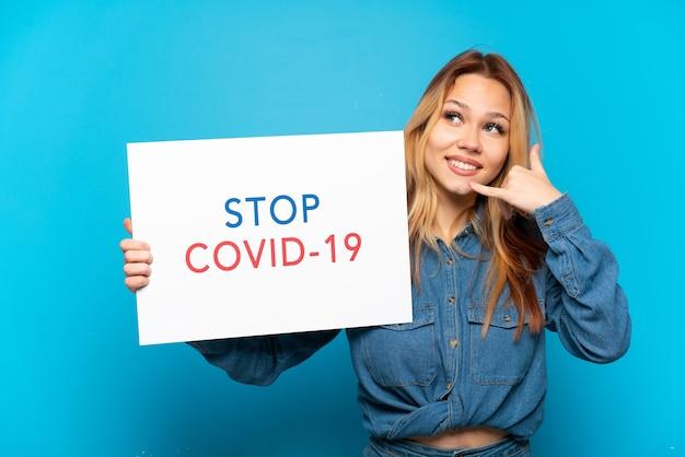 Nastoletnia dziewczyna trzymająca afisz z tekstem stop covid 19 i wykonująca gest telefoniczny na białym tle niebieski