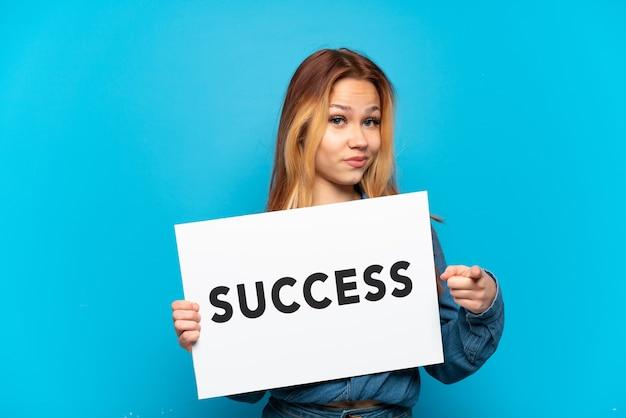 Nastoletnia dziewczyna trzymająca afisz z tekstem sukces i wskazująca do przodu na odosobnionym niebieskim tle