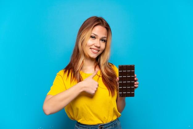 Nastoletnia dziewczyna trzymająca czekoladę na odosobnionym niebieskim tle, pokazująca gest kciuka w górę