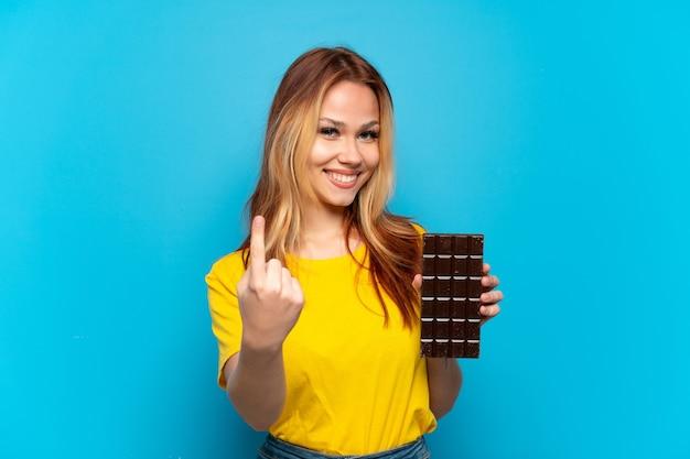 Nastoletnia dziewczyna trzymająca czekoladę nad odosobnionym niebieskim tłem, wykonująca nadchodzący gest