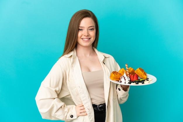 Nastoletnia dziewczyna trzymająca gofry na odosobnionym niebieskim tle pozuje z rękami na biodrach i uśmiecha się