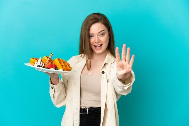 Nastoletnia dziewczyna trzymająca gofry na odosobnionym niebieskim tle szczęśliwa i licząca cztery palcami