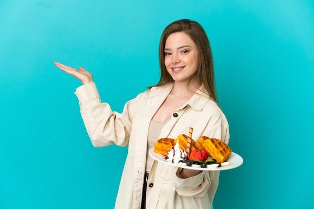 Nastoletnia dziewczyna trzymająca gofry na odosobnionym niebieskim tle, wyciągając ręce do boku, zapraszając do przyjścia