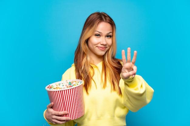 Nastoletnia dziewczyna trzymająca popcorny na białym tle szczęśliwa i licząca trzy palcami
