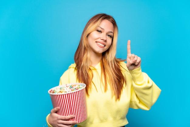 Nastoletnia dziewczyna trzymająca popcorny na odosobnionym niebieskim tle pokazująca i unosząca palec na znak najlepszych