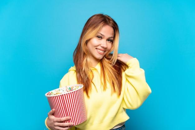 Nastoletnia dziewczyna trzymająca popcorny na odosobnionym niebieskim tle śmiejąca się