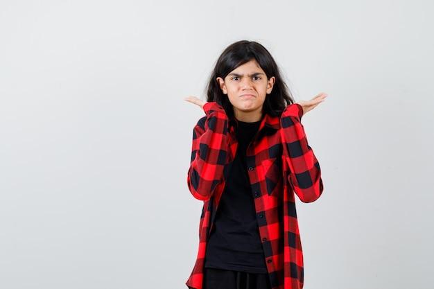 Nastoletnia dziewczyna trzymająca ręce podniesione, wzruszająca ramionami w koszulce, kraciastej koszuli i patrząca na rozczarowaną, widok z przodu.