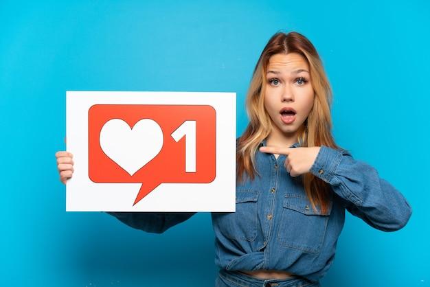Nastoletnia dziewczyna trzymająca tabliczkę z ikoną like i wskazującą ją na białym tle niebieski