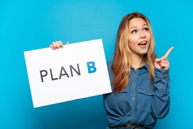 Nastoletnia dziewczyna trzymająca tabliczkę z napisem plan b i myśląca na odosobnionym niebieskim tle