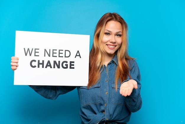 Nastoletnia dziewczyna trzymająca tabliczkę z tekstem potrzebujemy zmiany na odosobnionym niebieskim tle