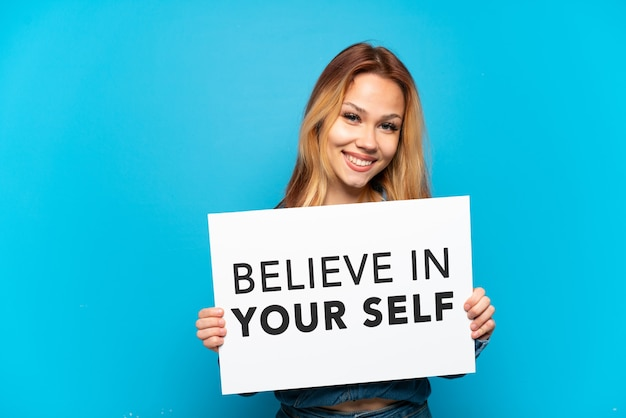 """Nastoletnia dziewczyna trzymająca tabliczkę z tekstem """"uwierz w siebie"""" z radosnym wyrazem twarzy na odosobnionym niebieskim tle"""