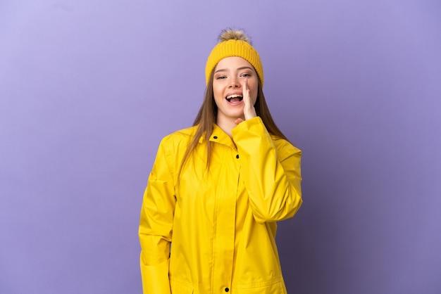 Nastoletnia dziewczyna ubrana w przeciwdeszczowy płaszcz na odosobnionym fioletowym tle krzycząca z szeroko otwartymi ustami