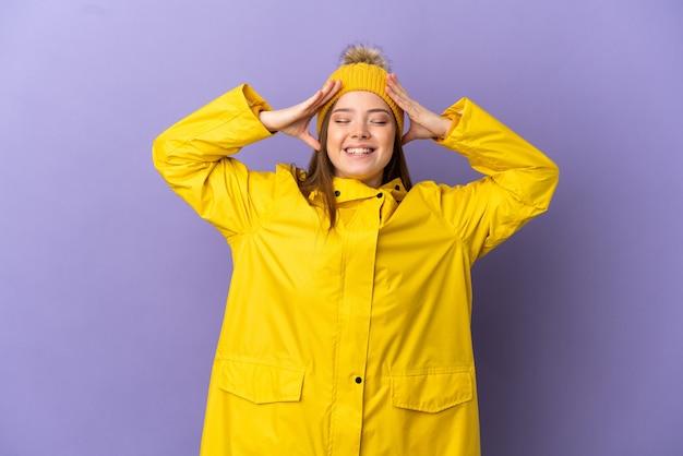 Nastoletnia dziewczyna ubrana w przeciwdeszczowy płaszcz na odosobnionym fioletowym tle z wyrazem niespodzianki