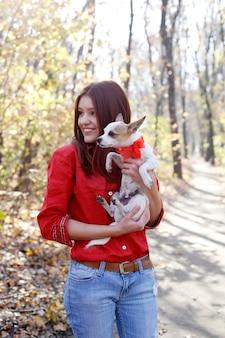 Nastoletnia dziewczyna uśmiecha się i przytula szczeniaka zabawki terier psa z kokardą