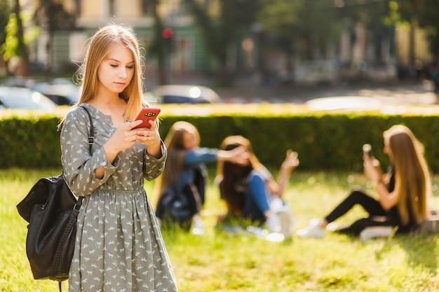 Nastoletnia dziewczyna używa smartphone w parku