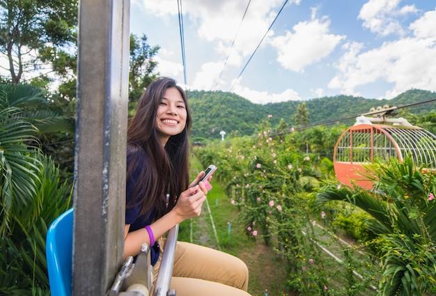 Nastoletnia dziewczyna używa technologia przyrząd w kraju dalekim terenie.