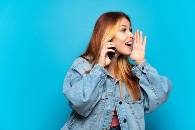 Nastoletnia dziewczyna używająca telefonu komórkowego na odosobnionym tle krzycząca z szeroko otwartymi ustami