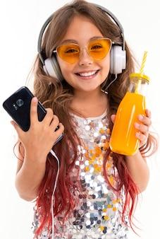 Nastoletnia dziewczyna w błyszczącej sukni i żółtych okularach przeciwsłonecznych, z dużymi białymi słuchawkami, słucha muzyki z czarnym smartfonem i butelką z sokiem pomarańczowym w dłoniach na białym tle