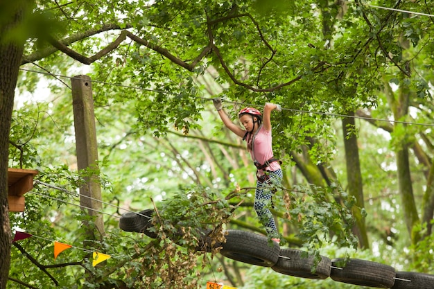 Nastoletnia dziewczyna w kasku i sprzęt bezpieczeństwa w parku linowym przygoda na tle natury