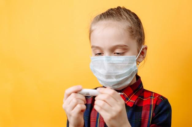 Nastoletnia dziewczyna w medycznej masce patrzy na termometr