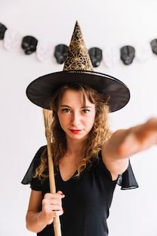 Nastoletnia dziewczyna w spiczastym kapeluszu z miotłą