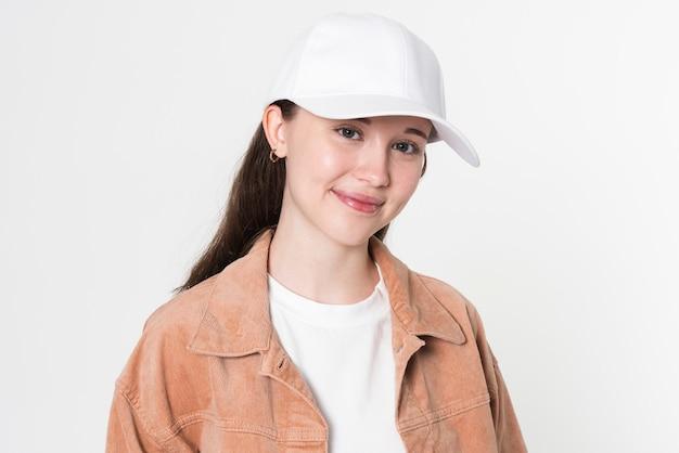 Nastoletnia dziewczyna w stylowym stroju i białej czapce portret studyjny do sesji zdjęciowej odzieży młodzieżowej