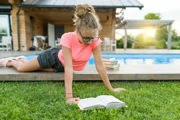 Nastoletnia dziewczyna w szkłach czyta książkę