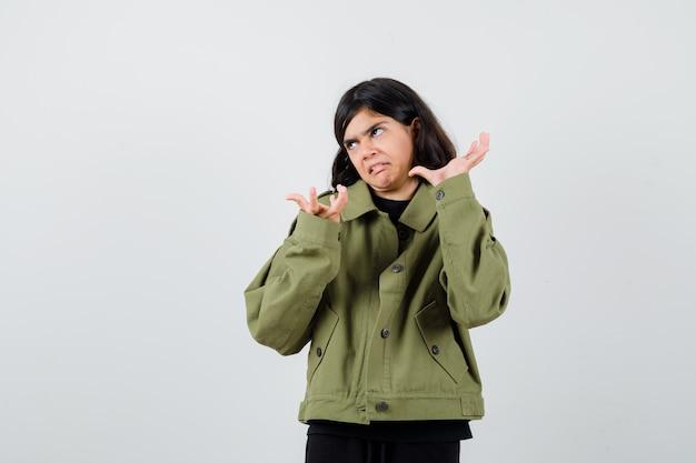 Nastoletnia dziewczyna wątpi, wzruszając ramionami w koszulce, kurtce i patrząc na skupiony widok z przodu.