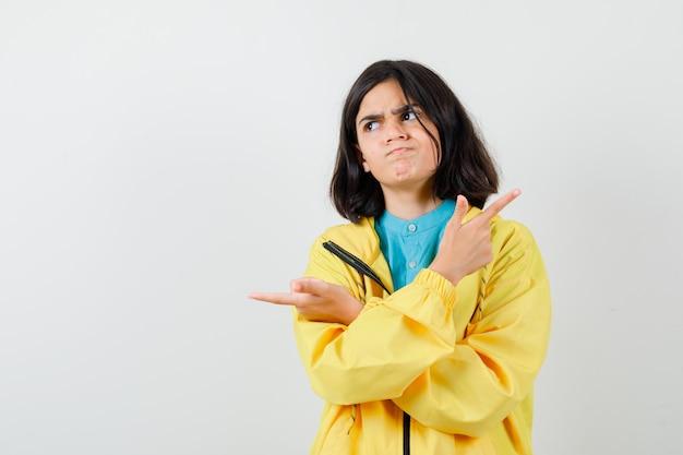 Nastoletnia dziewczyna wskazująca w przeciwnych kierunkach, odwracająca wzrok w żółtej kurtce i patrząca niezdecydowana. przedni widok.