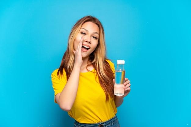 Nastoletnia dziewczyna z butelką wody na odosobnionym niebieskim tle krzyczy z szeroko otwartymi ustami