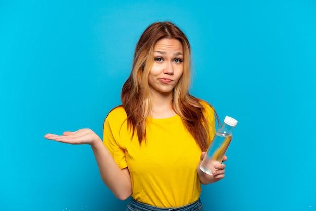 Nastoletnia dziewczyna z butelką wody na odosobnionym niebieskim tle ma wątpliwości podczas podnoszenia rąk
